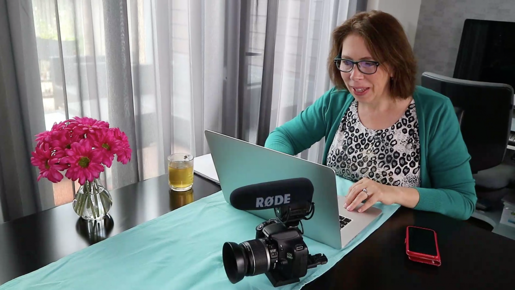 Anita van Agtmaal thuis aan het werk op laptop, met een kopje thee. Camera met Rode-microfoon erop bij de hand. Bosje roze bloemen erbij.